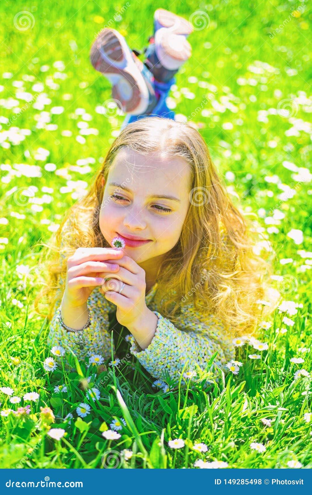 Gevoeligheidsconcept Het kind geniet de lente van zonnig weer terwijl het liggen bij weide met madeliefjebloemen Meisje op het gl