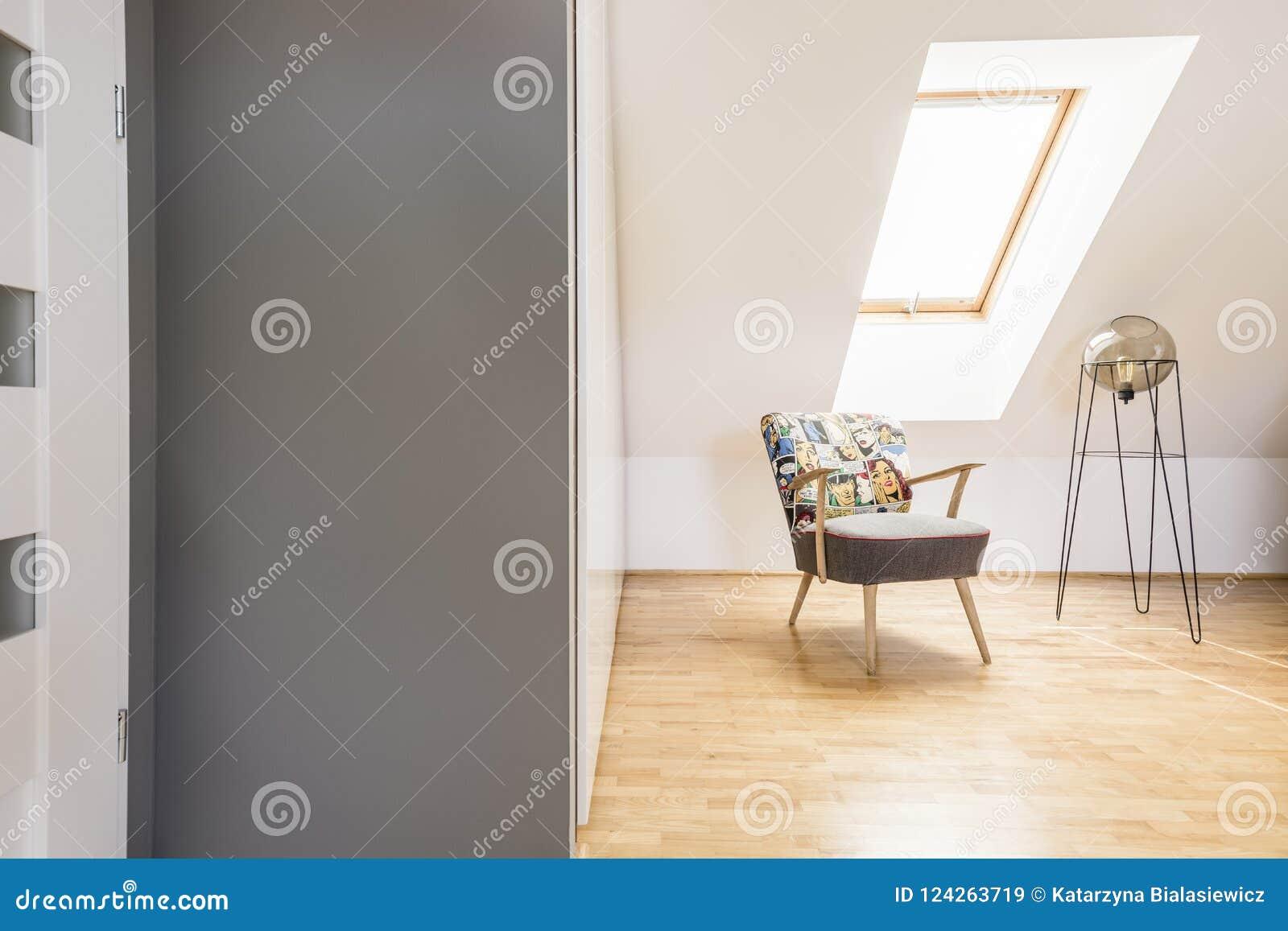 Gevormde leunstoel naast moderne lamp op houten vloer op zolder