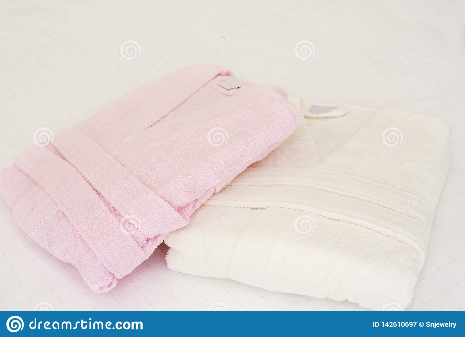 Gevouwen badjas op bed in ruimte Wit en roze, twee robes
