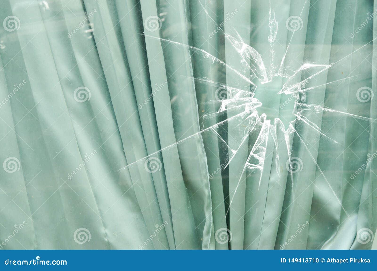 Gevouwen gordijnpatroon achter gebroken glas