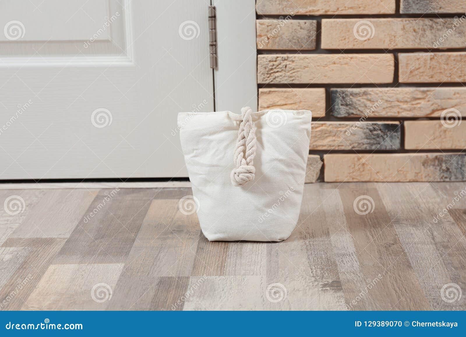 Gevulde zak dichtbij witte deur