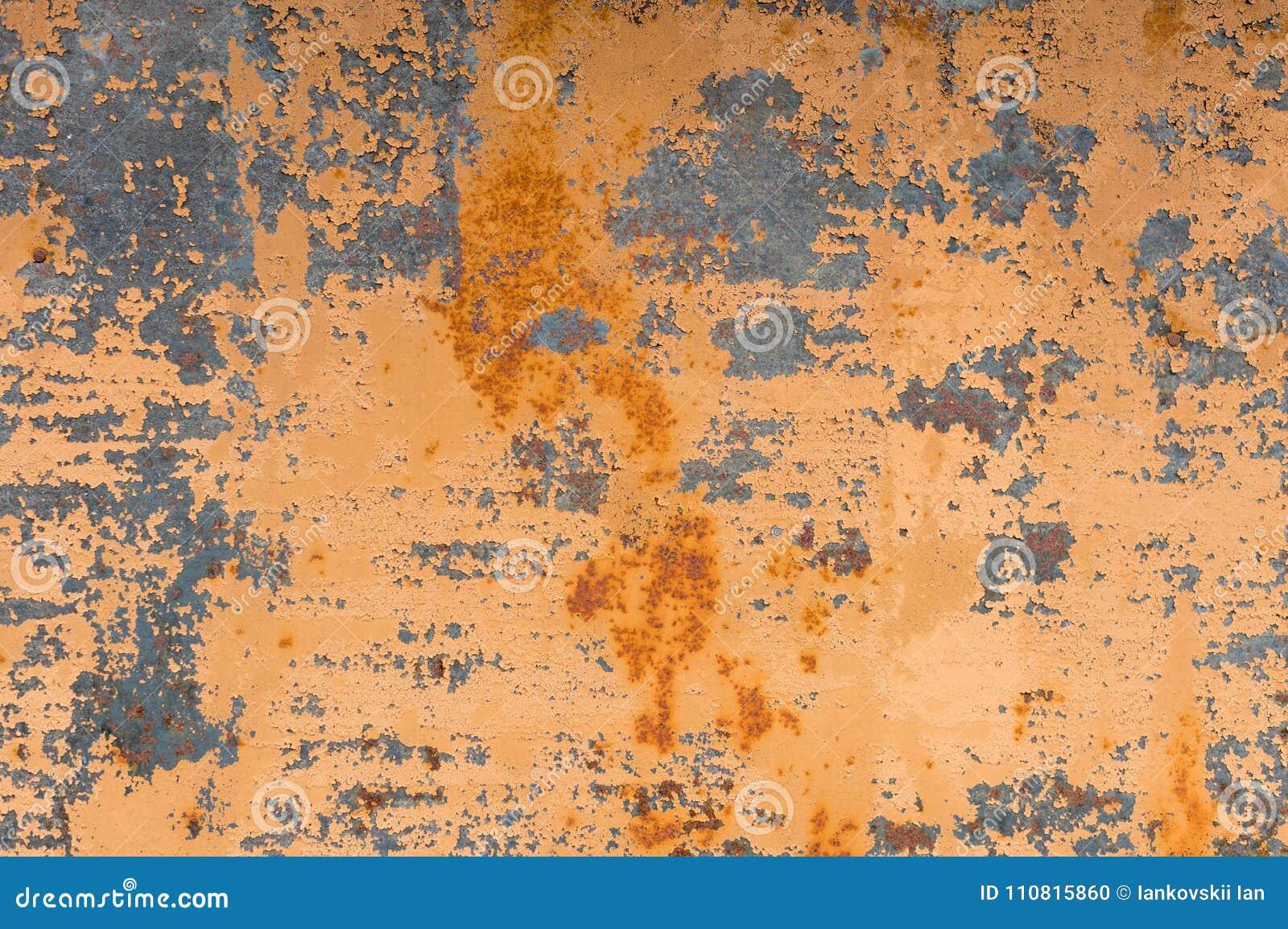 Geweven achtergrond van een langzaam verdwenen gele verf met geroeste barsten op geroest metaal Grungetextuur van een oud gebarst