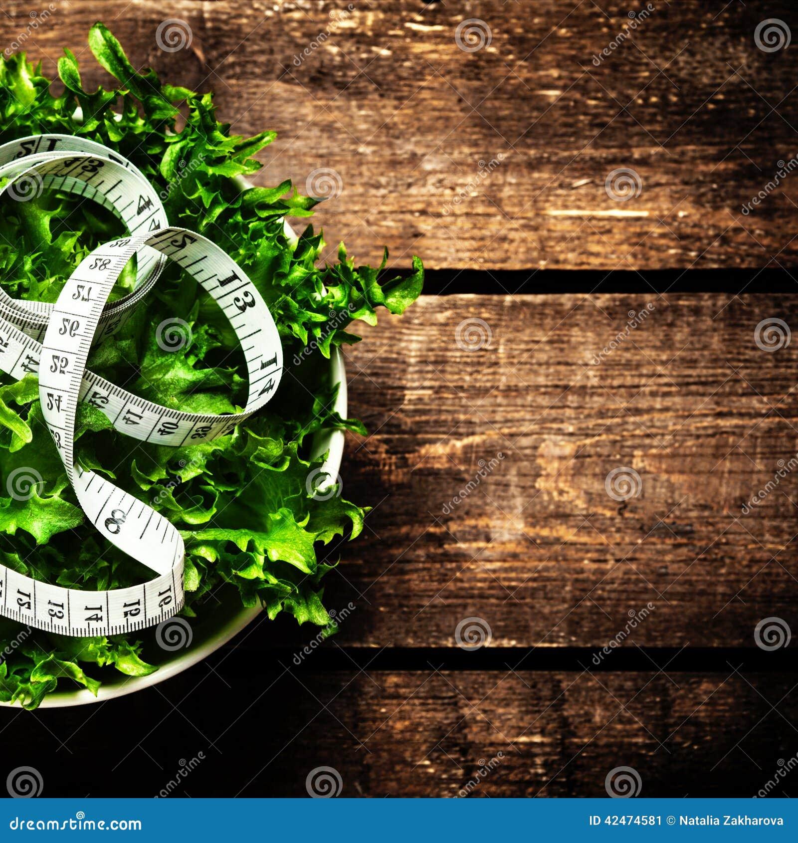 Gewichtsverlust-Salat und messendes Band über hölzernem Hintergrund Di