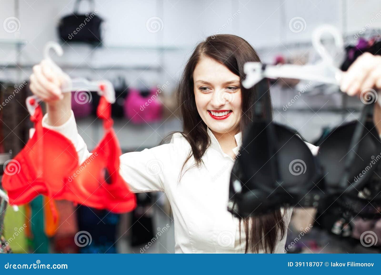 Gewoon meisje die bustehouder kiezen bij manierwinkel