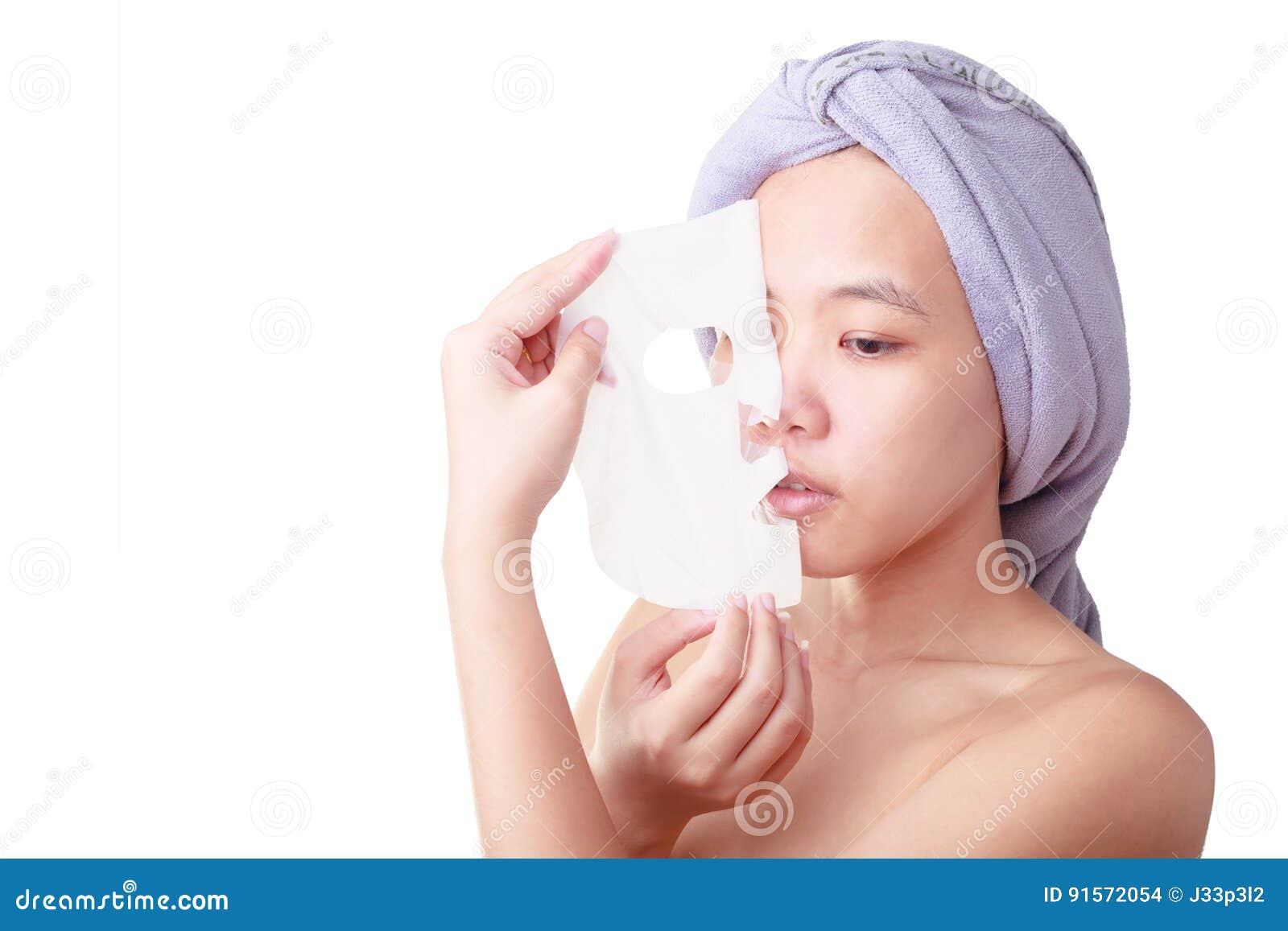 Gezicht van de close-up het Aziatische jonge vrouw, meisje die gezichtsschil verwijderen van masker dat op wit wordt geïsoleerd