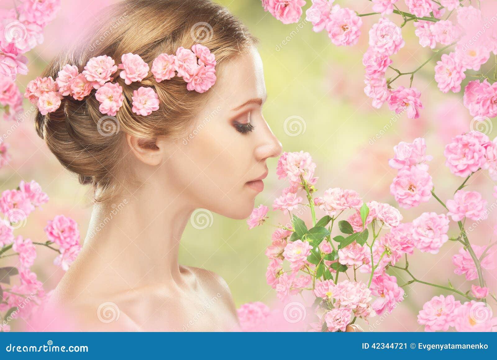 Gezicht van jonge mooie vrouw met roze bloemen in haar haar