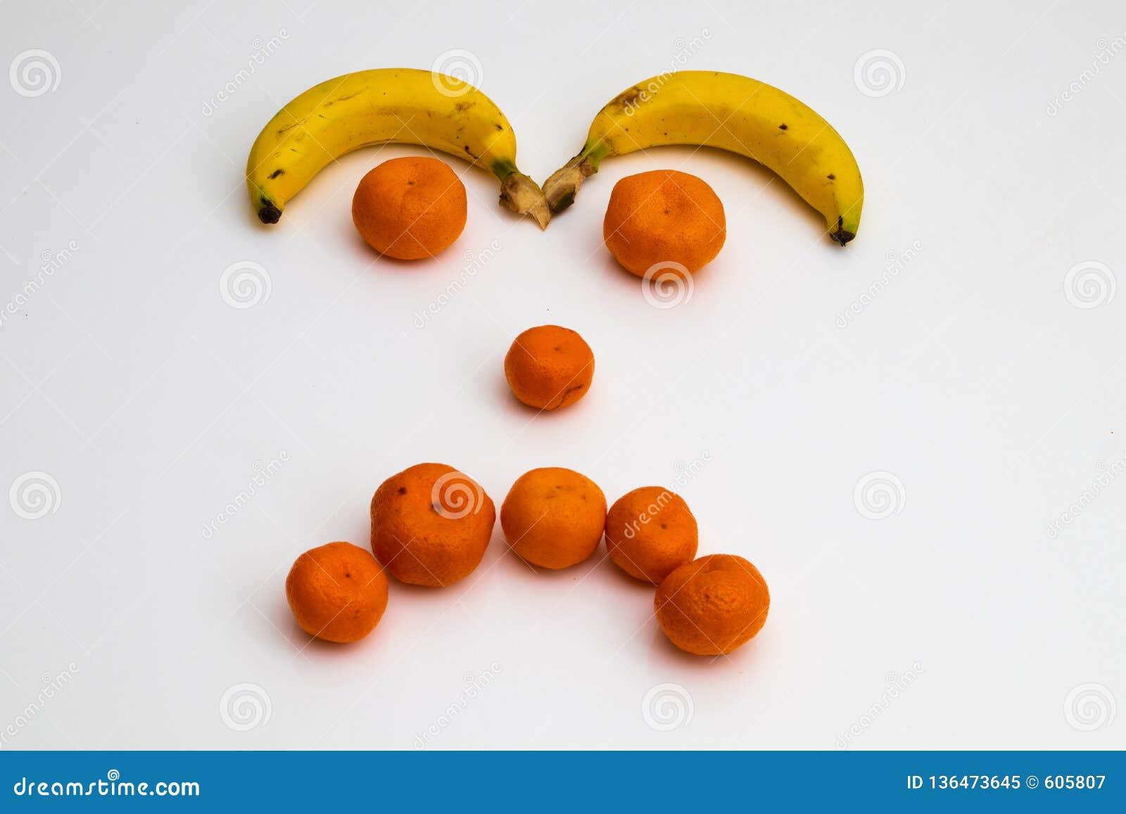 Gezicht van vruchten op witte achtergrond gezicht met verse vruchten wordt gemaakt die banaan, mandarin mandarijn