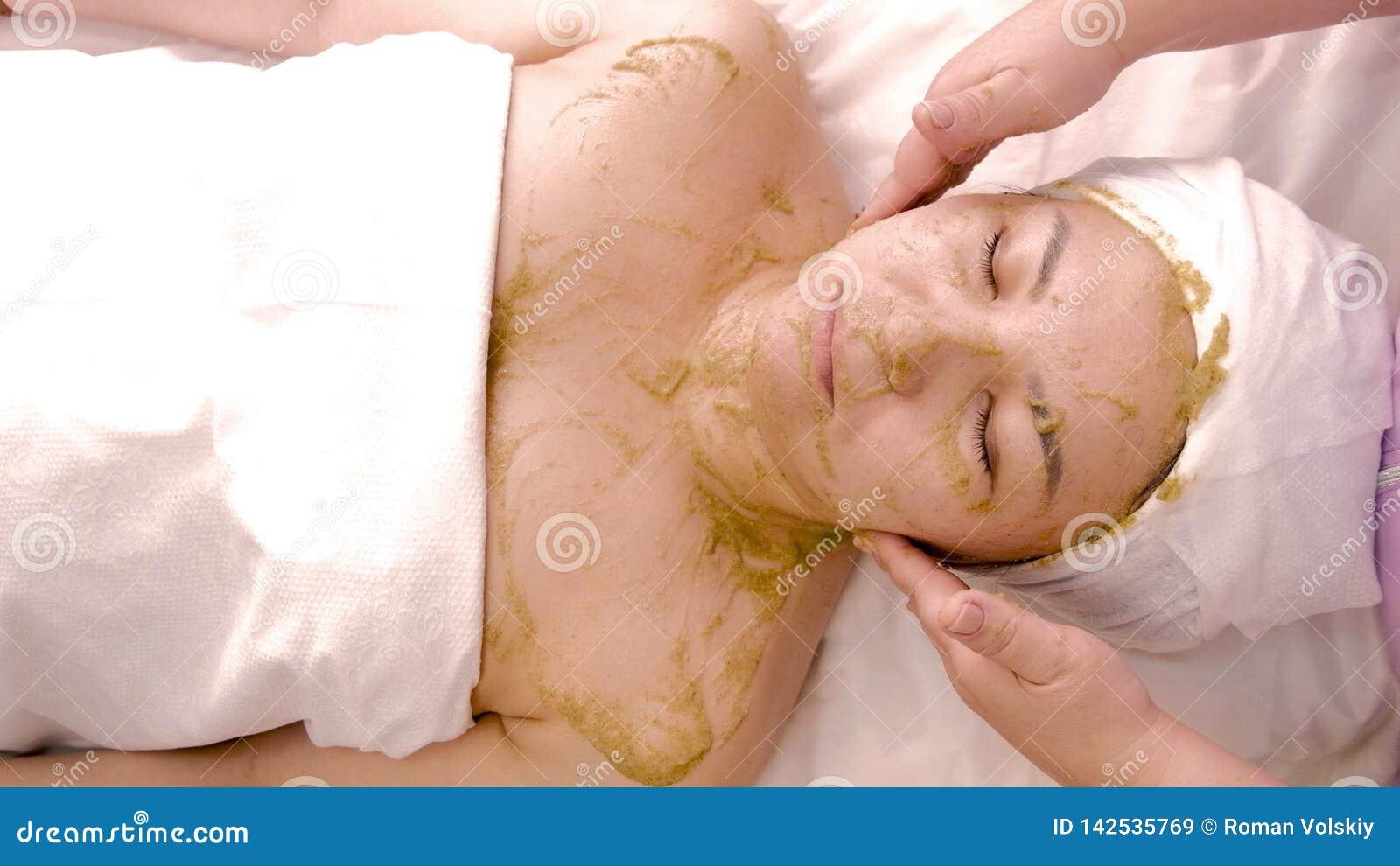Gezichts kosmetisch die masker op groene algen wordt gebaseerd Ontspannen Aziatische vrouw die in kuuroord rusten cosmetology Lic