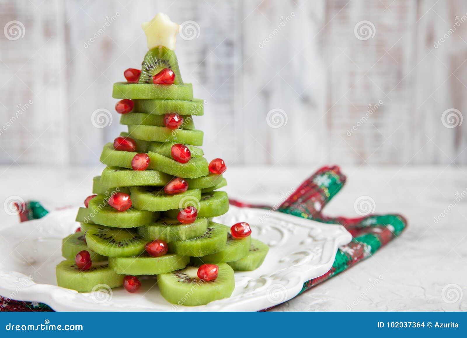 Gezond dessertidee voor jonge geitjespartij - de grappige eetbare Kerstboom van de kiwigranaatappel