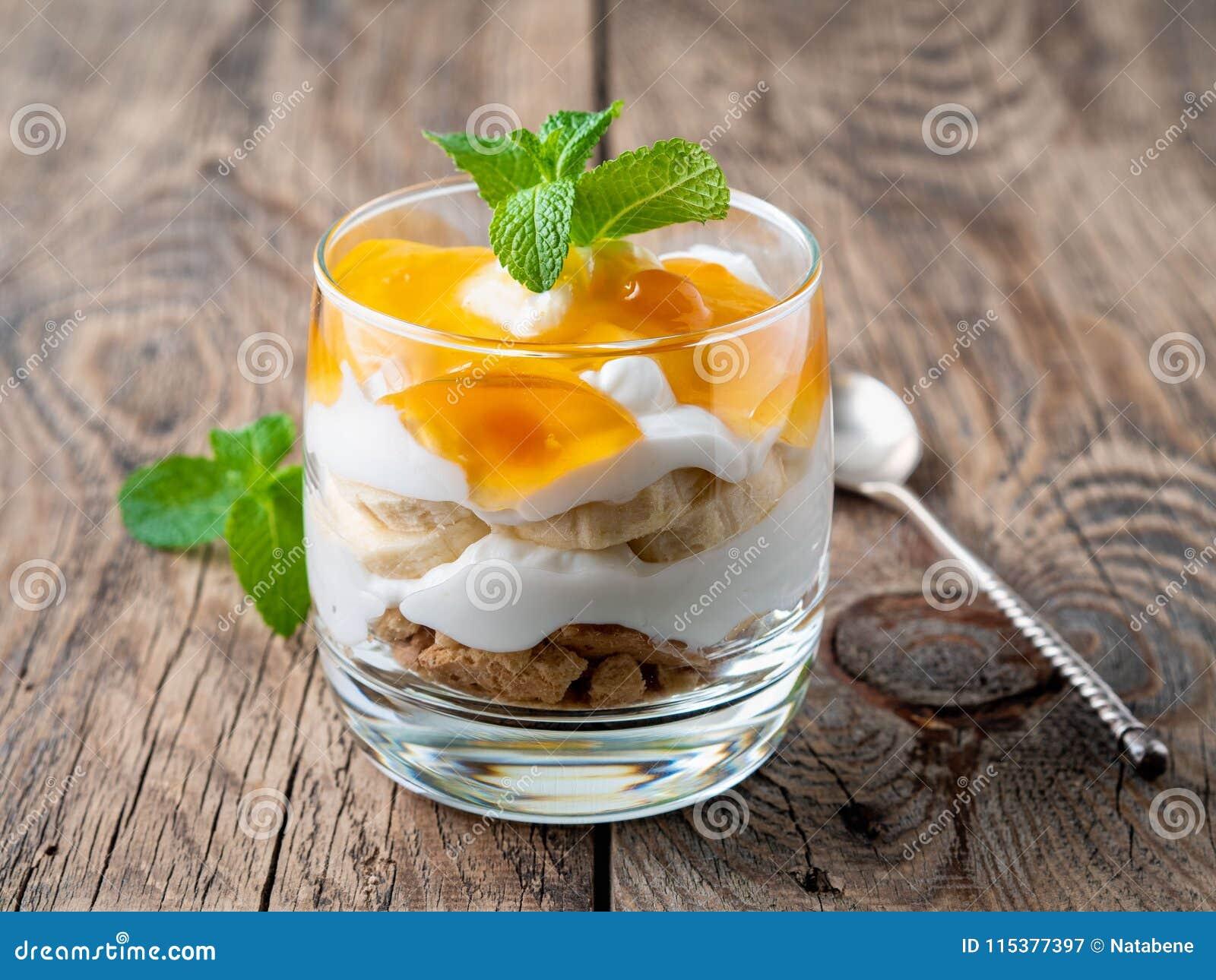 Gezond gelaagd dessert met yoghurt, banaan, mango, koekje op houten achtergrond, zijaanzicht