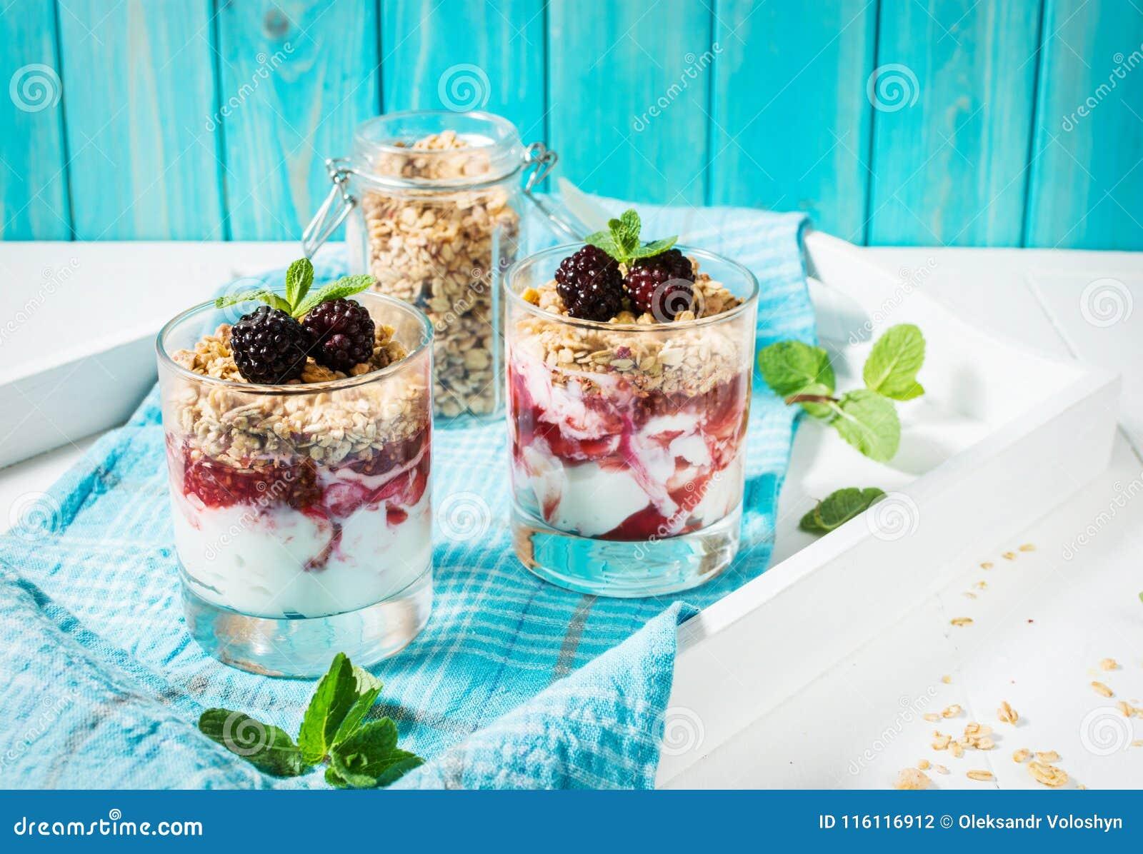Gezond gelaagd dessert met yoghurt, granola, jam, braambes in glas op houten achtergrond