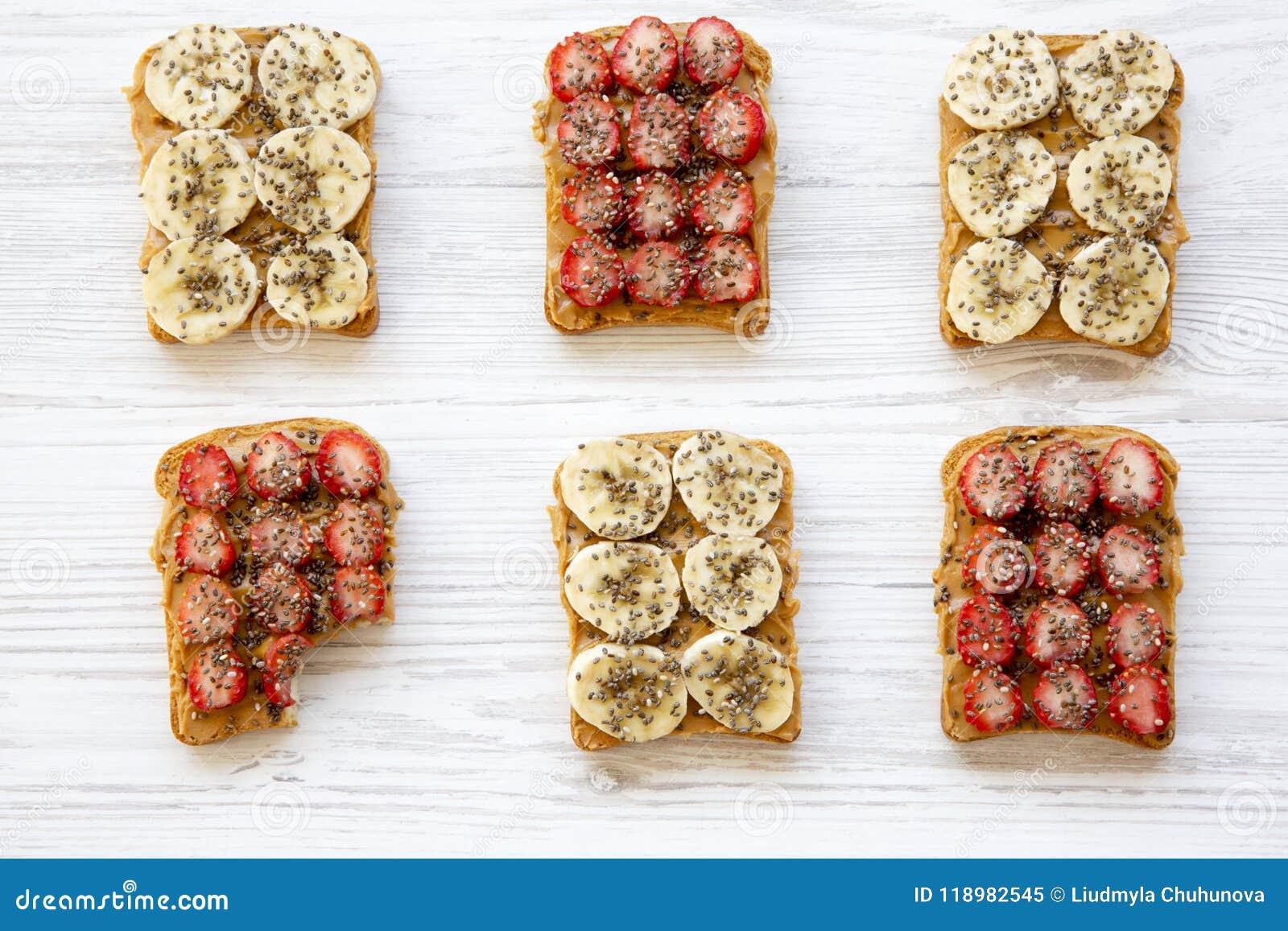 Gezond ontbijt, het op dieet zijn concept Veganisttoosts en één gebeten toost met vruchten, zaden, pindakaas op witte houten acht