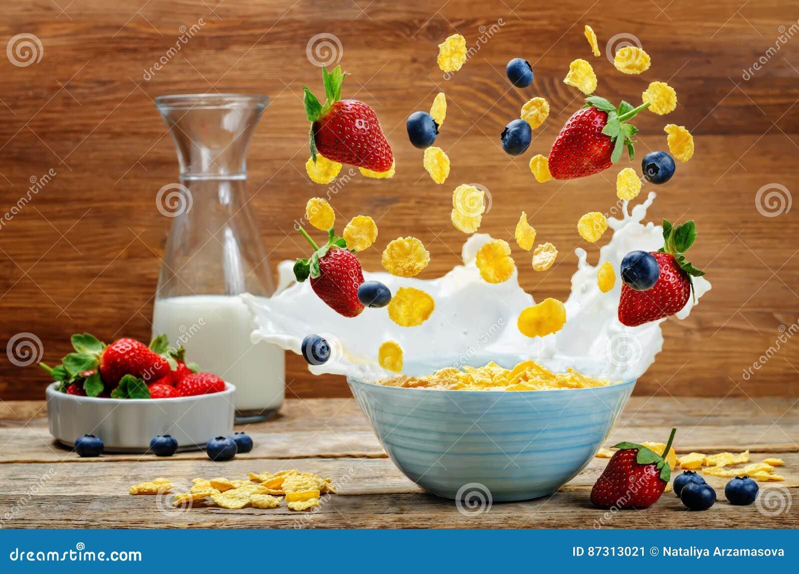 Gezond ontbijt met melk, vliegende cornflakes, aardbeien
