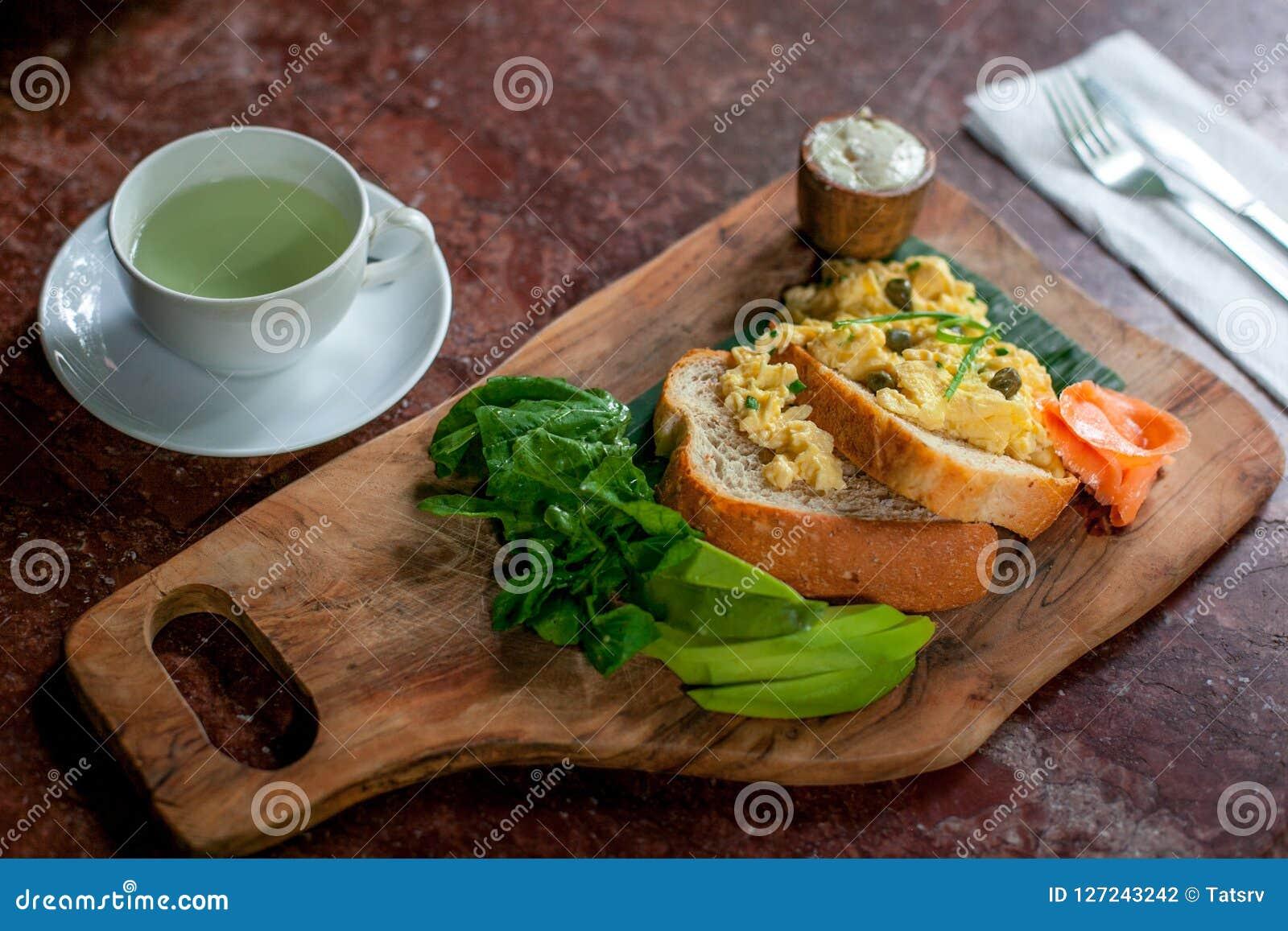 Gezond Ontbijt met Volkorenbroodtoost en Roereieren met avokado, kaas en zalm op scherpe raad en groene thee