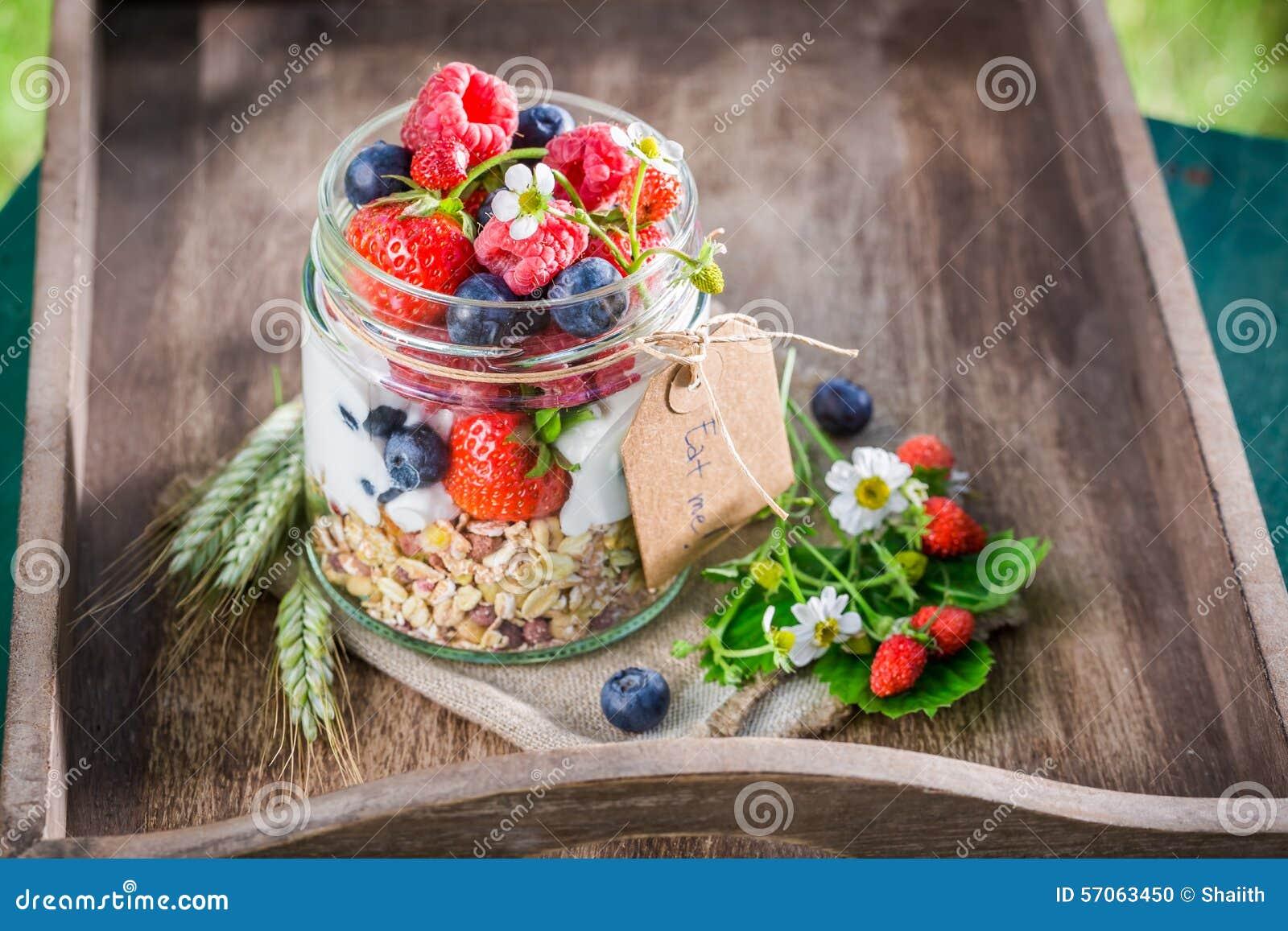 Gezond ontbijt met yoghurt en bessen in zonnige dag