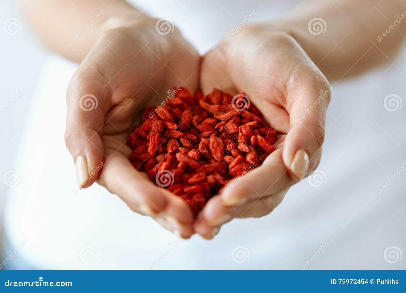 Gezond Organisch Dieetvoedsel Het Hoogtepunt van vrouwenhanden van Goji-Bessen
