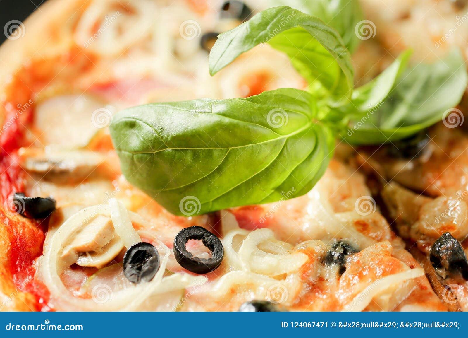 Gezond voedsel Sluit omhoog voedselbeeld van basilicum op Italiaanse pizza Macro fotografie Het eten van achtergrond
