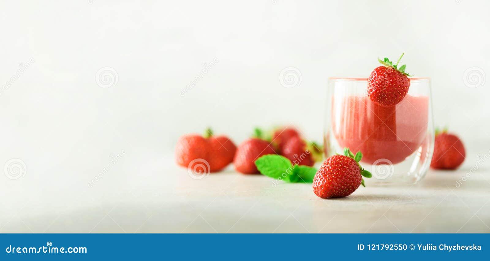 Gezonde aardbei smoothie in glas op grijze achtergrond met exemplaarruimte banner De zomervoedsel en schoon het eten concept