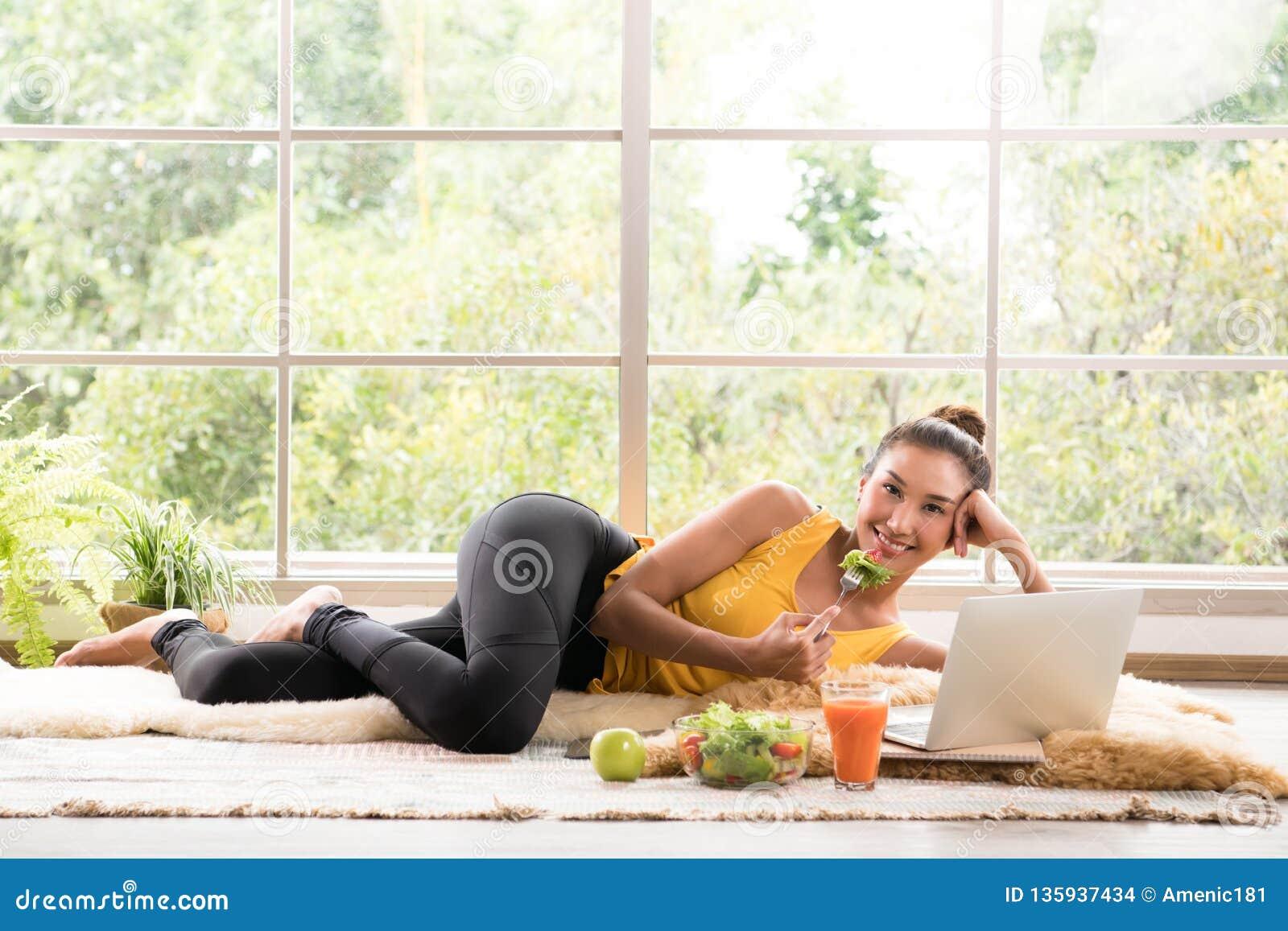 Gezonde Aziatische vrouw die op de vloer liggen die salade eten en camera bekijken