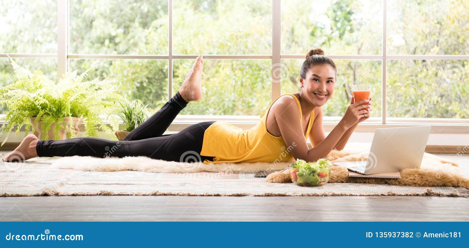 Gezonde Aziatische vrouw die op de vloer liggen die salade eten die ontspannen en comfortabel kijken