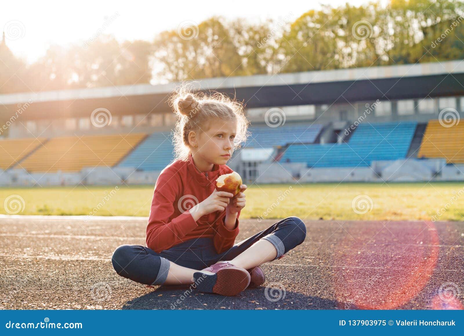 Gezonde levensstijl en gezond voedselconcept Weinig mooi meisjeskind die in sportkleding appelzitting op stadion daarna eten