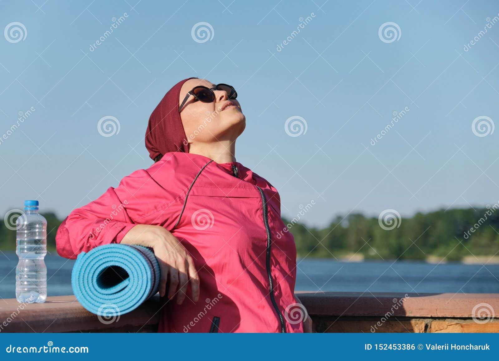 Gezonde levensstijl van rijpe vrouw, openluchtportret van een leeftijdswijfje in sportkleding met yogamat en fles water