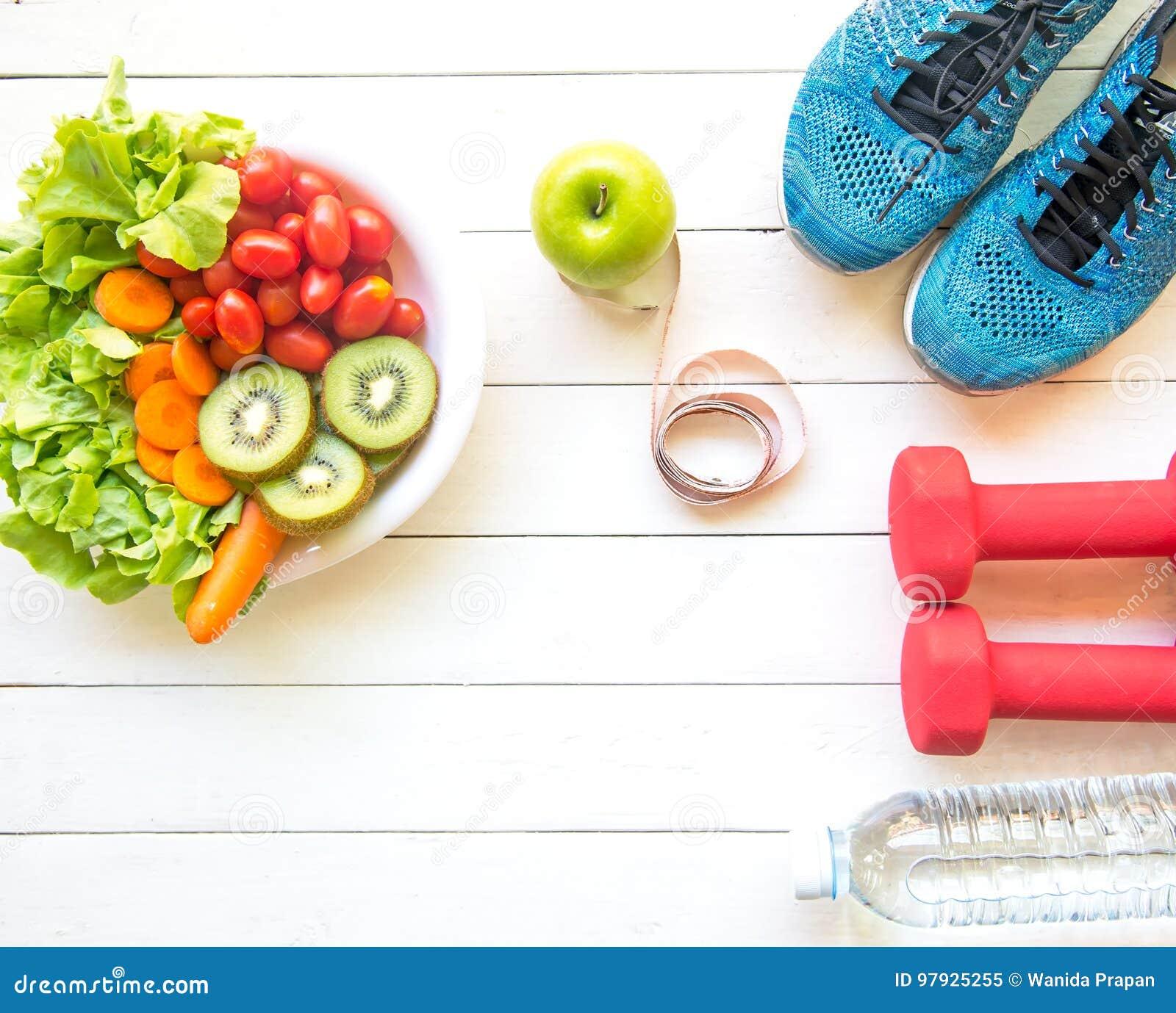 Gezonde levensstijl voor vrouwendieet met sportmateriaal, tennisschoenen, die band, plantaardige verse, groene appelen en fles wa