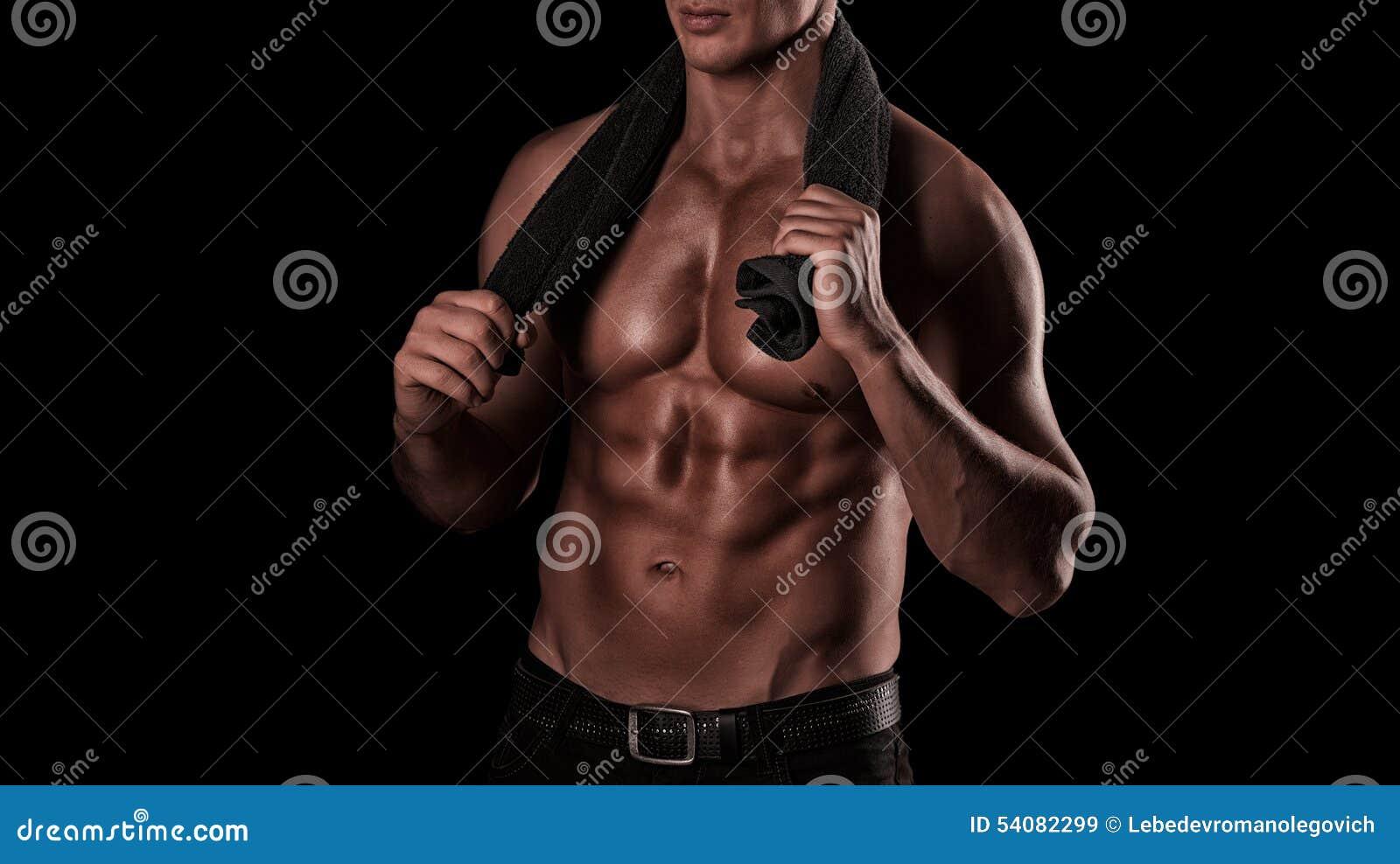 Gezonde spier jonge mens na een training op donkere achtergrond