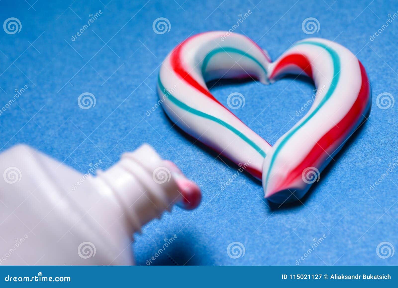 Gezonde tanden Hygiëne van de mondholte Gekleurde tandpasta van een buis Deegwaren in de vorm van een hart