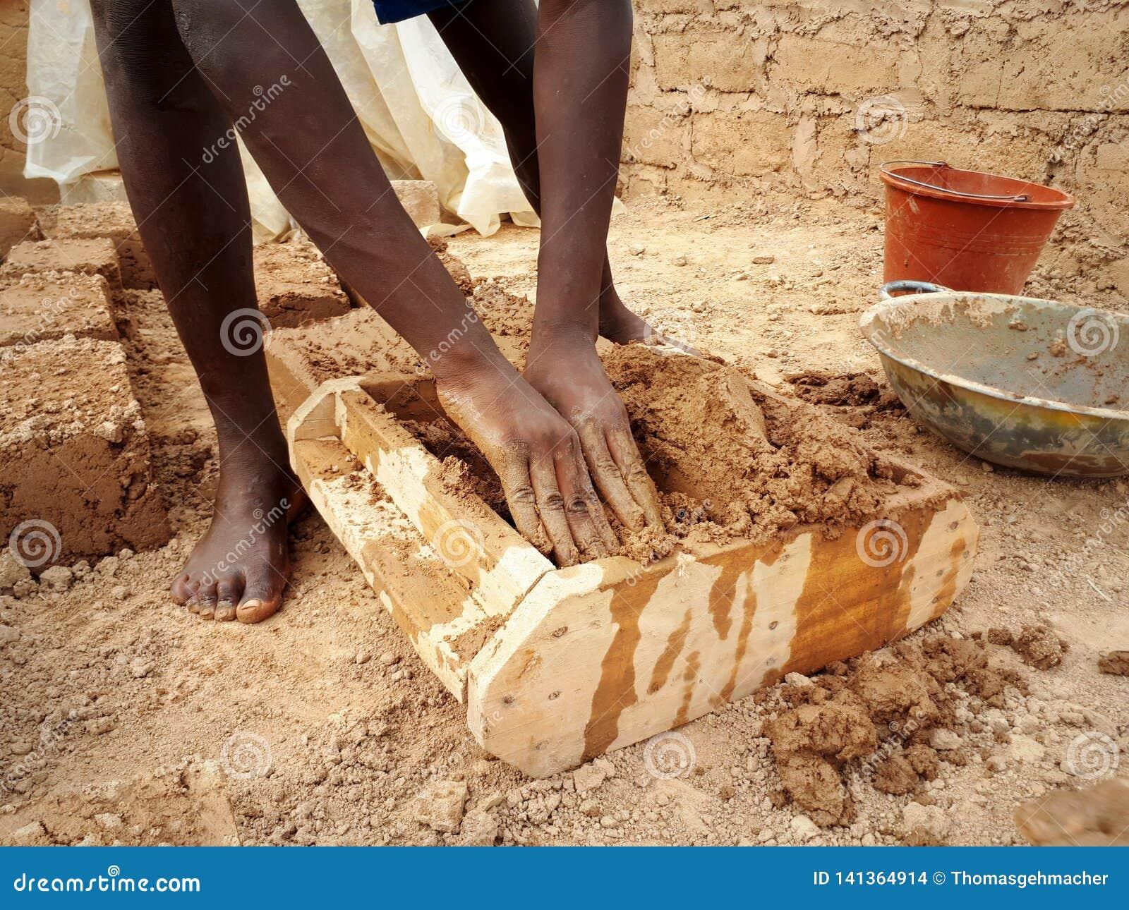 Ghanese arbeider die modderbaksteen vormen