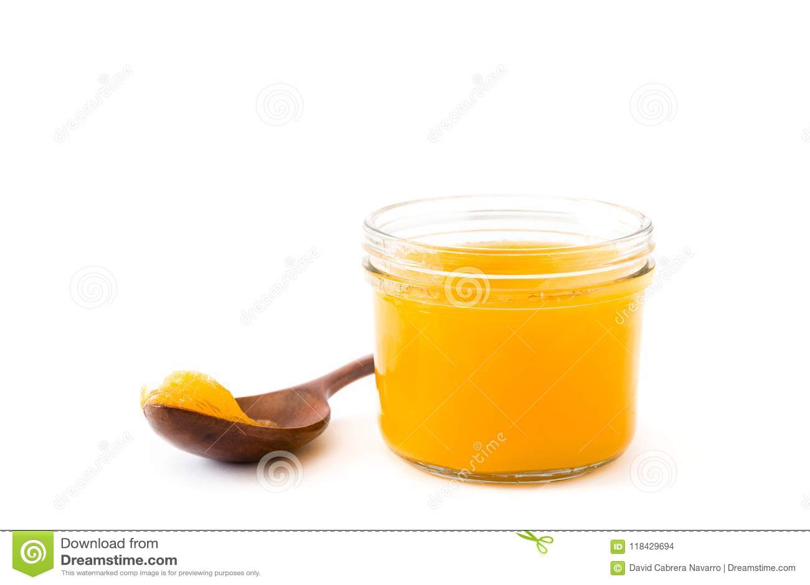 Ghee ή διευκρινισμένο βούτυρο στο βάζο και το ξύλινο κουτάλι που απομονώνονται