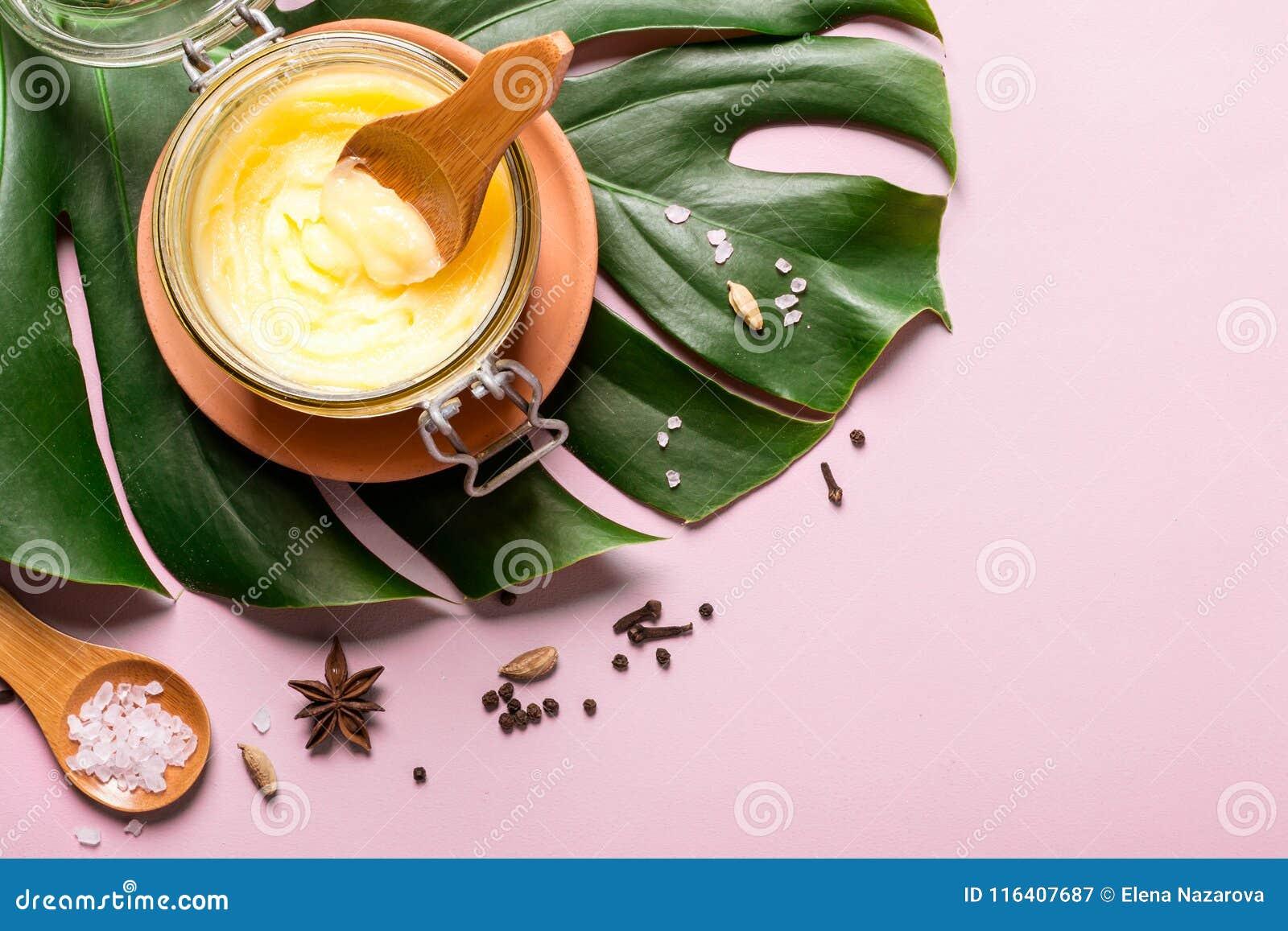 Ghee βούτυρο σε ένα βάζο γυαλιού, ένα ρόδινα άλας και καρυκεύματα στο ρόδινο υπόβαθρο