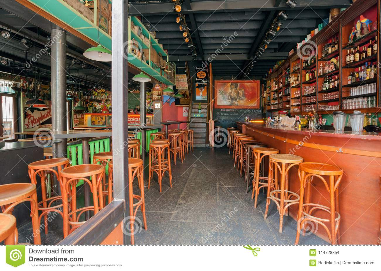 empty bar with wooden tables bottles drinks and colorful