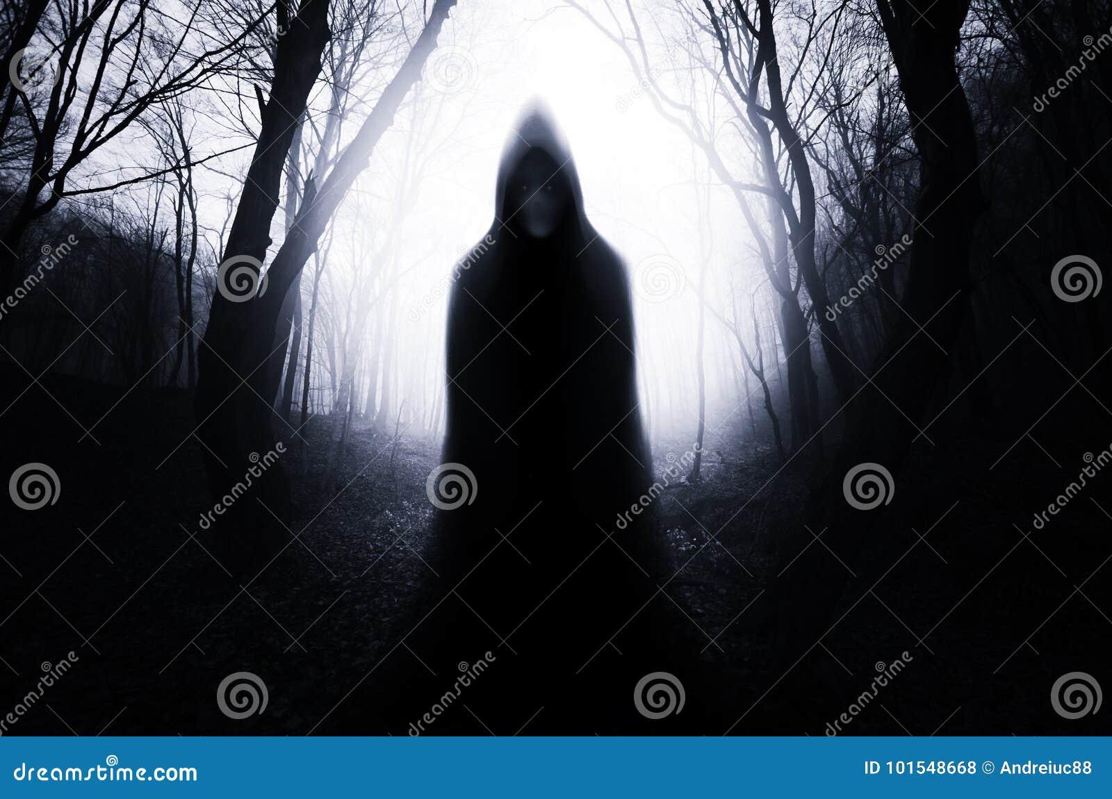Ghost in dark haunted forest on Halloween