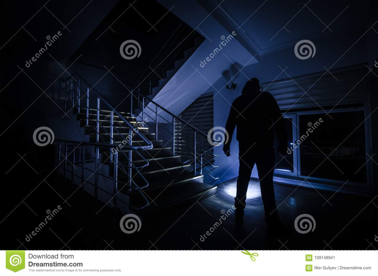 Ghost in Haunted House at stairs, Mysterious silhouette of ghost man with light at stairs, Horror scene of scary ghost spooky llig