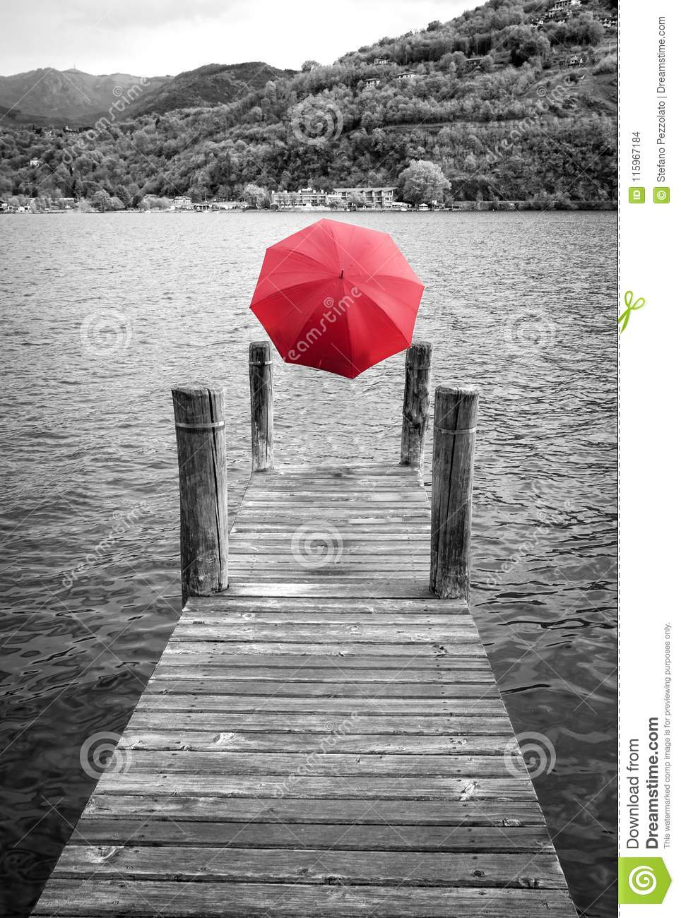A ghost with a red umbrella on the shores of lake orta piedmont northern italy add film effect