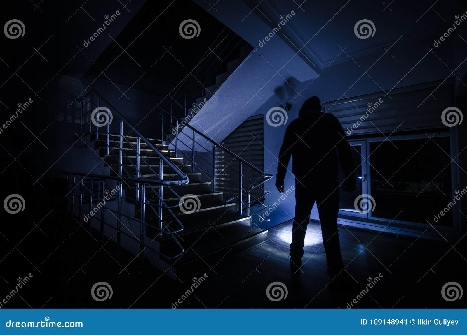 Ghost na casa assombrada em escadas, silhueta misteriosa do homem do fantasma com luz em escadas, cena do horror do llig assustad