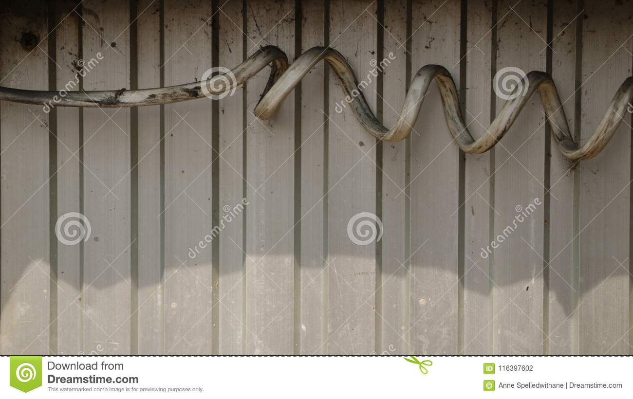 Thick Dirty Spiral Electrical Wire On Corrugated Steel Wall Stock