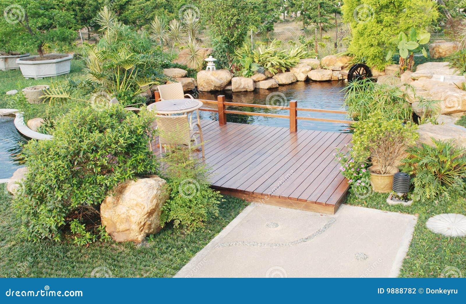Un giardino privato con il pergola di legno sopra uno stagno di pesci ...