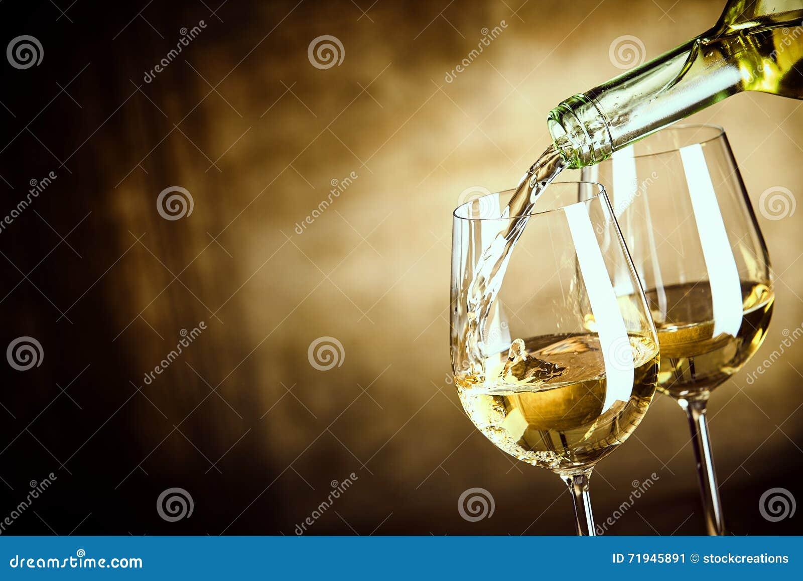Gießen von zwei Gläsern Weißwein von einer Flasche