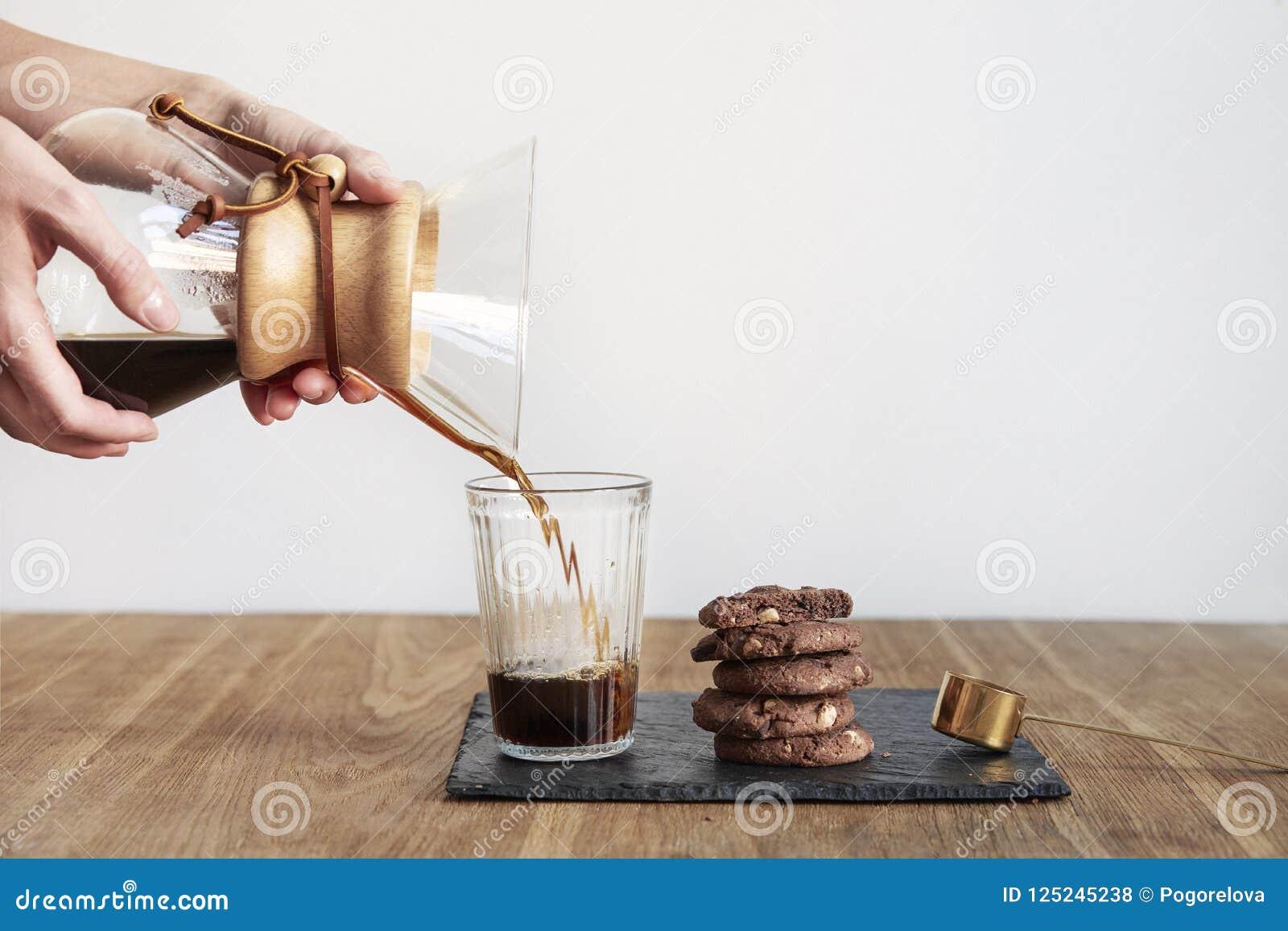 Giet over koffie brouwende methode Chemex, de greep van vrouwenhanden een glaskom, stilleven met browniekoekjes op houten lijst