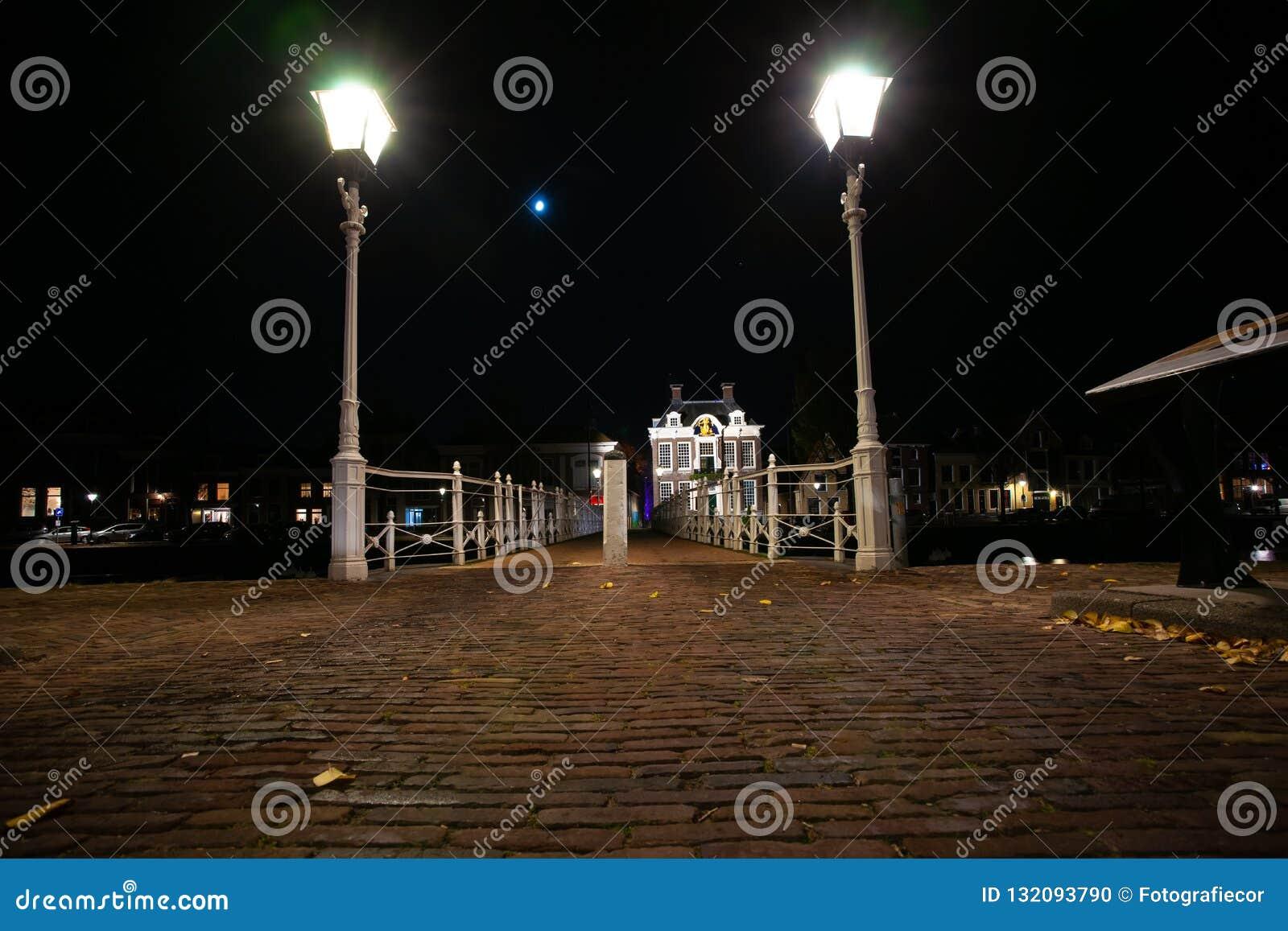 Gietijzer gesmede brug in de haven met straatverlichting en o