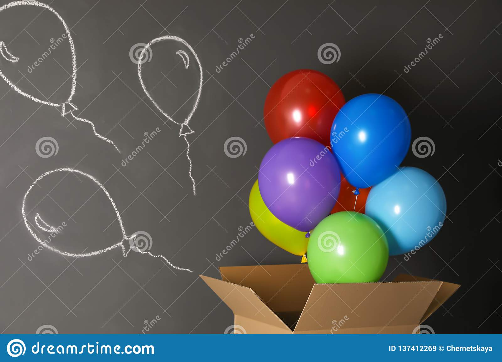 Gift box with bright air balloons and chalk drawing