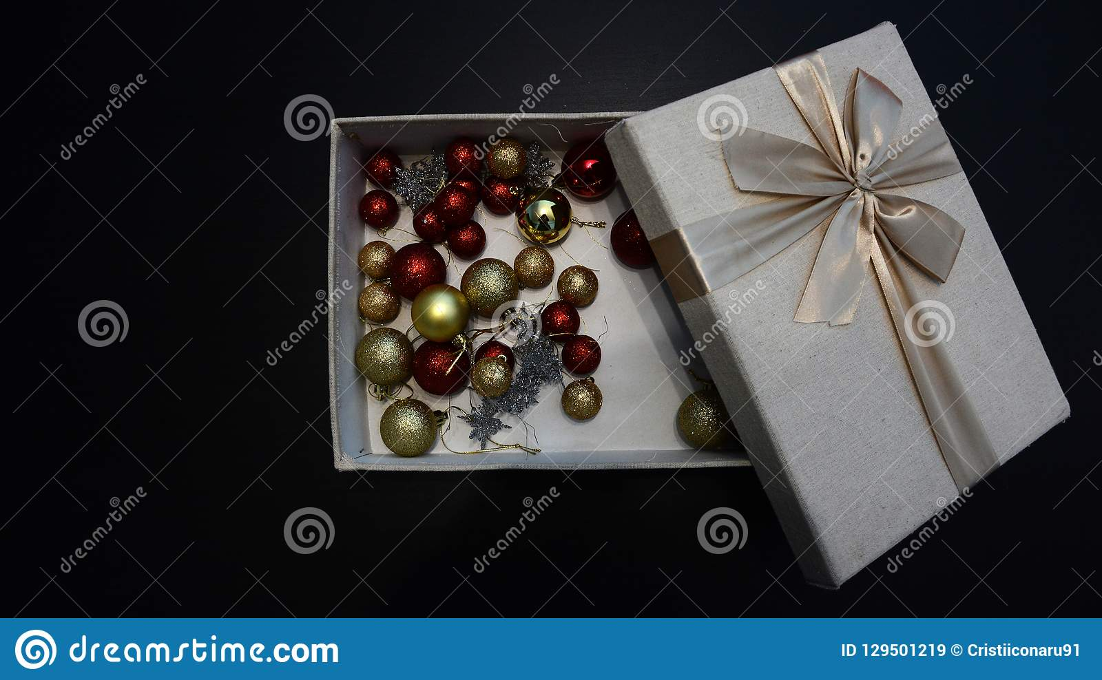 Gift box with Christmas globes inside against dark background