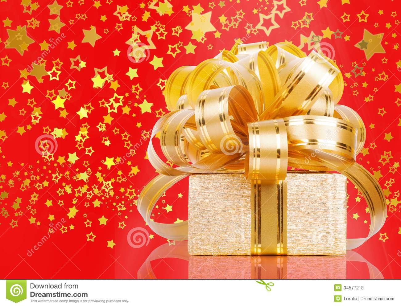 Gift box in gold wrapping paper on a beautiful red abstract background
