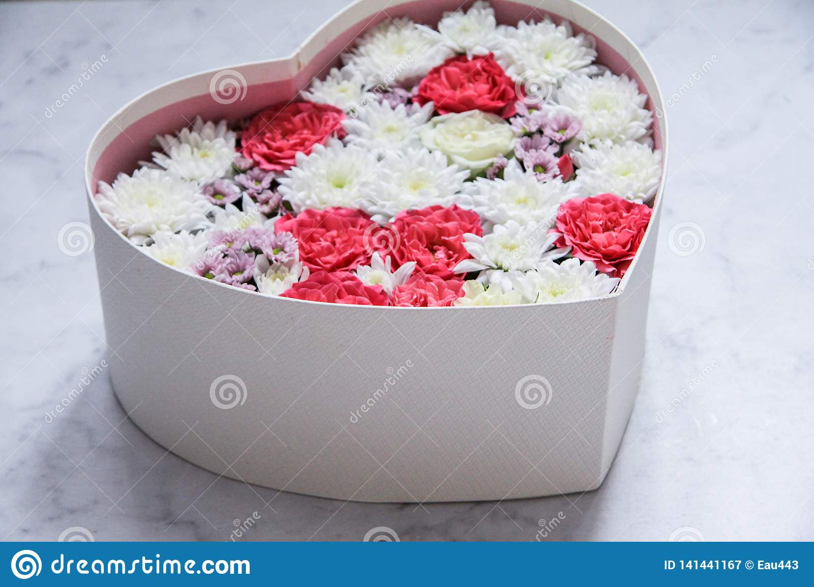 Gift box with heart shaped flowers on grey marble background