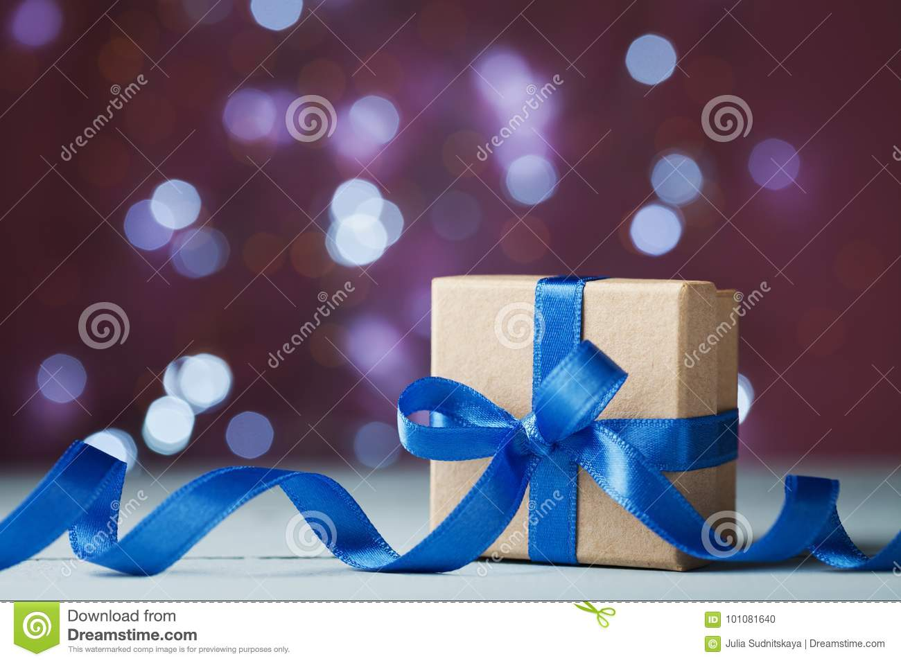 Gift box or present against festive bokeh background. Holiday greeting card for Christmas, New Year or birthday.