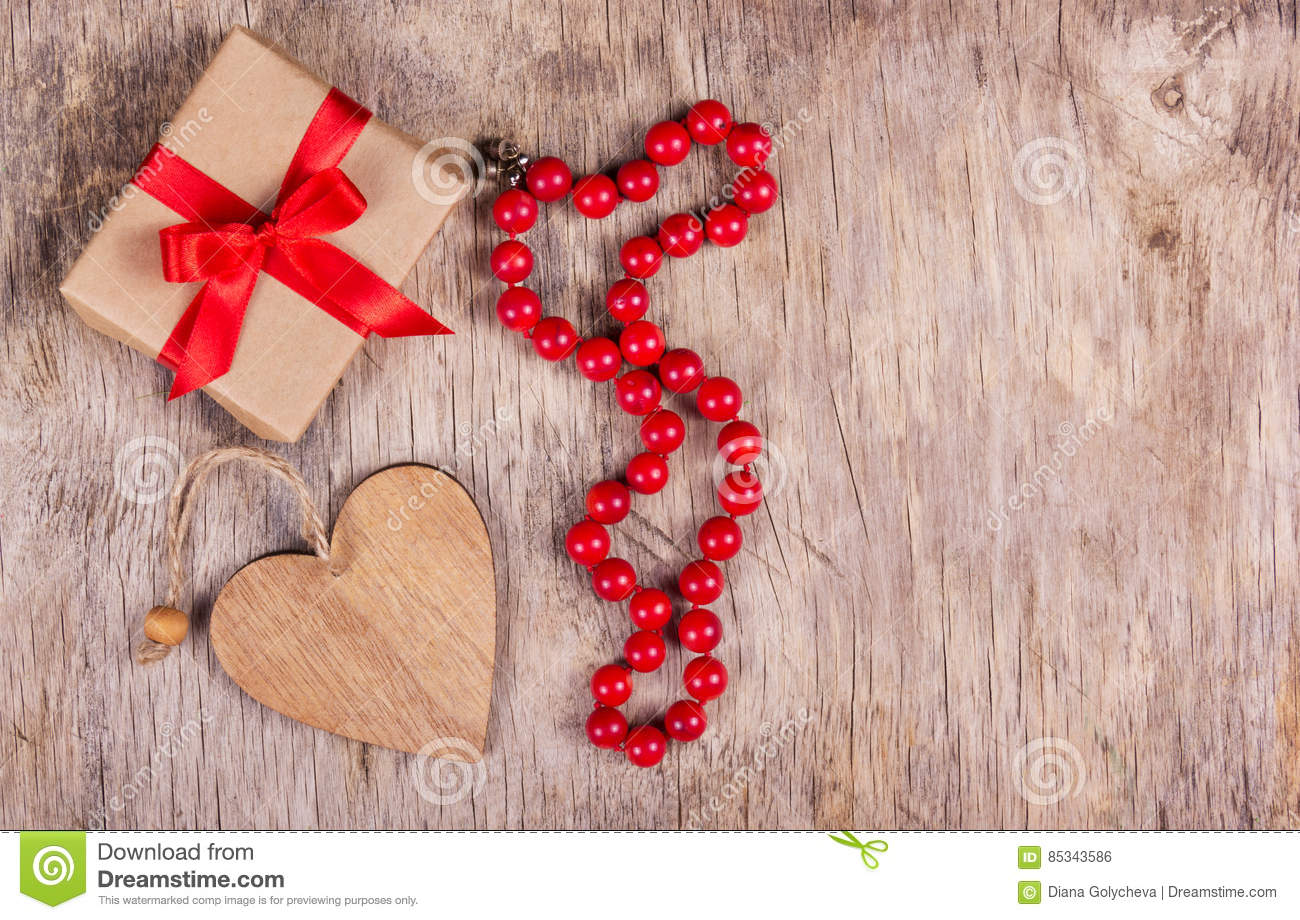 Gift box with red bow, valentine and coral necklace on the old wooden background. St. Valentine`s Day. Copy space