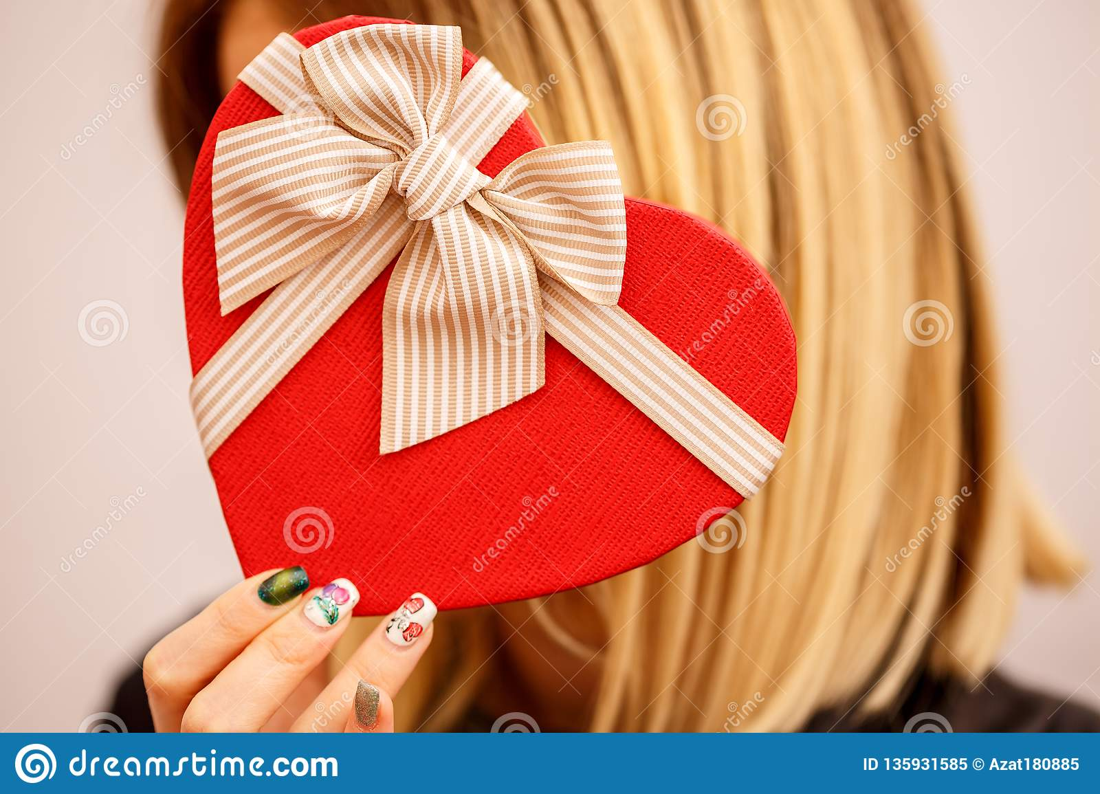 Gift box with a ribbon in female hands. The concept is suitable for love stories, birthdays and Valenti