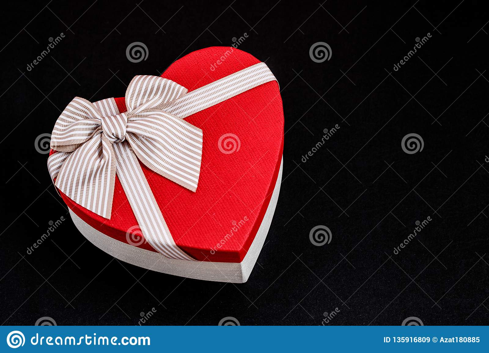 Gift box in the shape of a heart with a ribbon on a bla background. The concept is suitable for love stories, birthdays and Valent